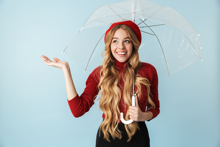 Portrait of friendly blond woman 20s with long hair standing under umbrella while isolated over blue background in studio 写真素材