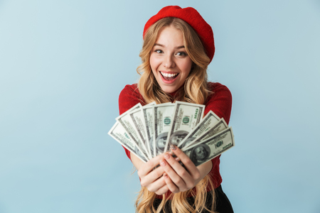 Photo of excited blond woman 20s wearing red beret holding bunch of money banknotes isolated over blue background in studio