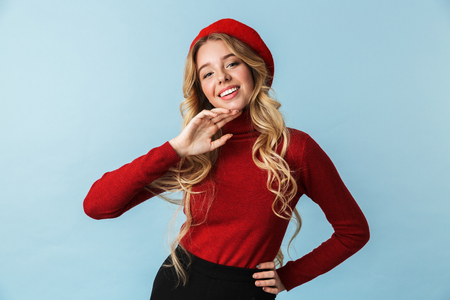 Portrait of caucasian blond woman 20s wearing red beret smiling while standing isolated over blue background in studio