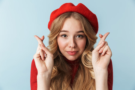 Image of attractive blond woman 20s wearing red beret keeping fingers crossed while standing isolated over blue background in studio