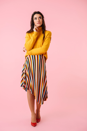 Full length of a beautiful pensive young woman wearing colorful clothes standing isolated over pink background