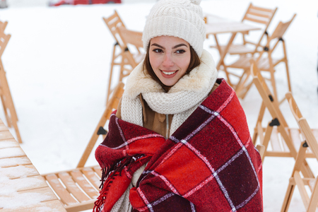 Afbeelding van een mooie jonge vrouw in muts en sjaal die buiten in de wintersneeuw loopt en een plaid draagt. Stockfoto