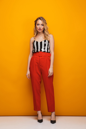 Full length portrait of a beautiful young blonde woman standing over yellow background, posing Stock fotó