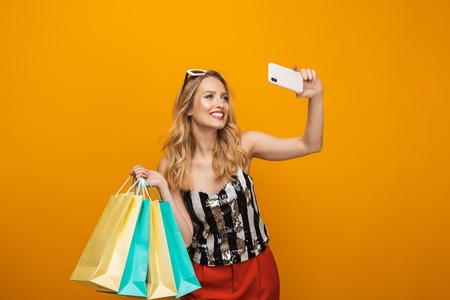 Portrait of a beautiful young blonde woman standing isolated over yellow background, taking a selfie