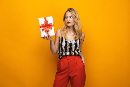 Portrait of a beautiful upset young blonde woman standing isolated over yellow background, showing present box