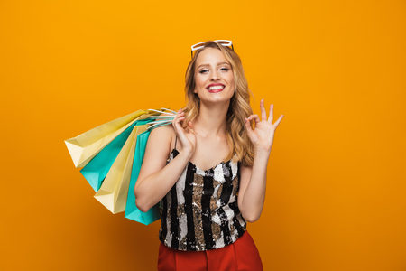 Portrait of a beautiful young blonde woman standing isolated over yellow background, ok