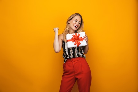 Portrait of a beautiful young blonde woman standing isolated over yellow background, showing present box Stock fotó