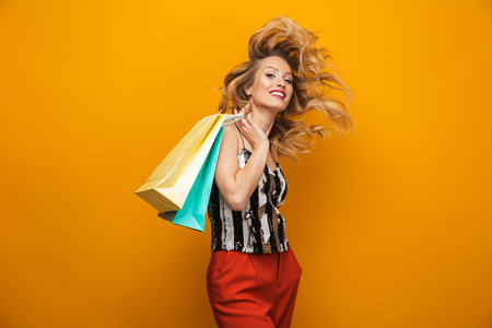 Portrait of a beautiful young blonde woman standing isolated over yellow background, carrying shopping bags 版權商用圖片