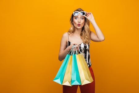 Portrait of a beautiful young blonde woman standing isolated over yellow background, carrying shopping bags Stock Photo