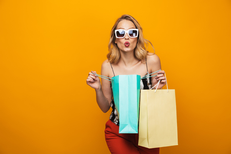 Portrait of a beautiful young blonde woman standing isolated over yellow background Stock Photo