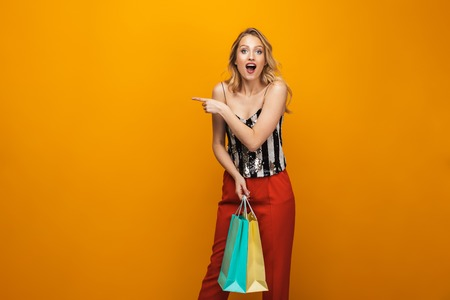Portrait of a beautiful young blonde woman standing isolated over yellow background, carrying shopping bags, pointing away