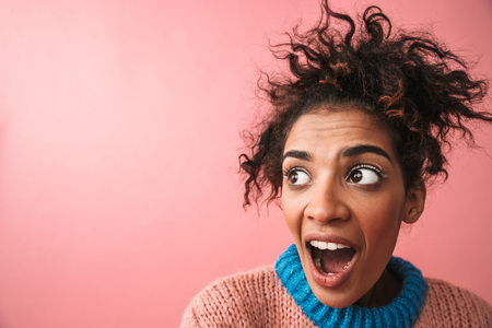 Image of shocked emotional beautiful young african woman posing isolated over pink wall background.