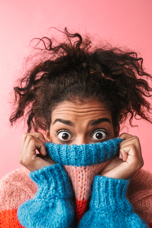 Image of a shocked beautiful young african woman posing isolated over pink wall background covering face with sweater. Imagens