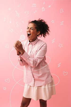 Image of a beautiful young african woman posing isolated over pink wall background screaming singing.
