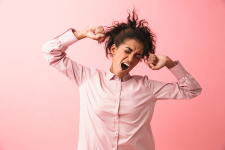 Image of a beautiful young african woman posing isolated over pink wall background stretching yawning.