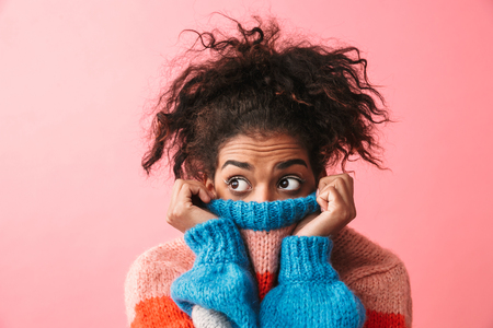 Image of a shocked beautiful young african woman posing isolated over pink wall background covering face with sweater. Stock Photo