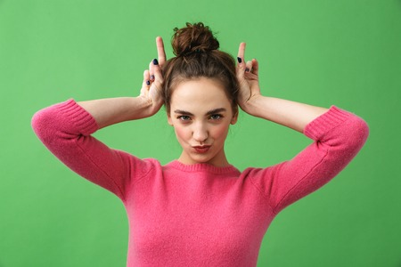 Portrait of an upset young woman standing isolated over green background
