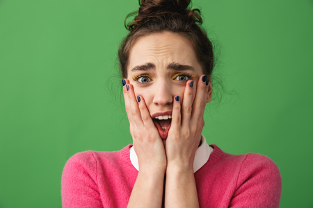 Portrait of a shocked young woman standing isolated over green background