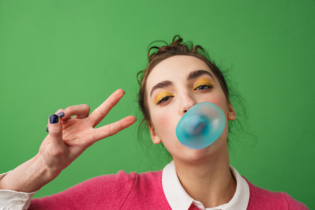 Portrait of a cheerful young woman standing isolated over green background, blowing chewing gum Stok Fotoğraf