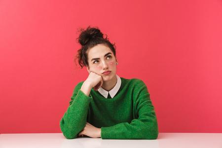 Schönes junges Studentenmädchen, das am Tisch lokalisiert über rosa Hintergrund sitzt und wegschaut