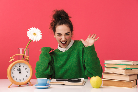 Beautiful young nerd student girl sitting at the table isolated over pink background, studying with books, celebrating success Banque d'images