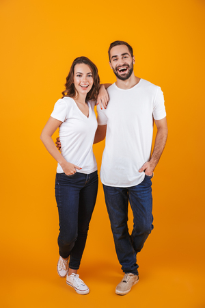 Full length photo of beautiful couple smilings while standing isolated over yellow background