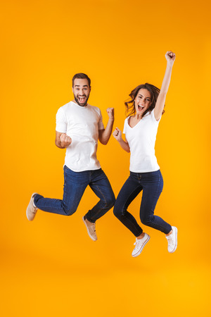 Full length photo of rejoicing couple screaming in surprise while jumping isolated over yellow background