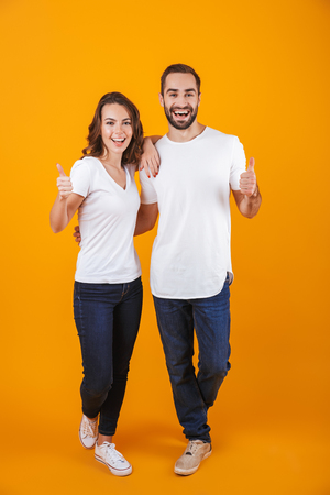 Full length photo of excited couple smilings while standing isolated over yellow background