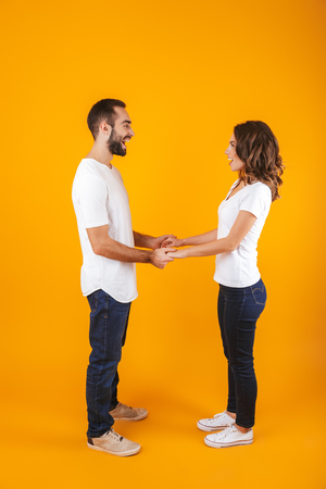 Full length photo of beautiful couple laughing and holding hands isolated over yellow background
