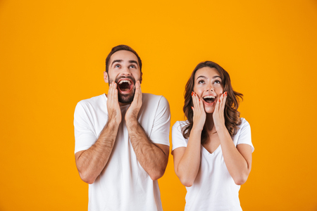 Image of happy people man and woman in basic clothing screaming in surprise and touching cheeks isolated over yellow background