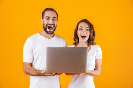 Portrait of lovely man and woman holding silver laptop while standing isolated over yellow background