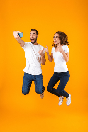 Full length photo of content couple laughing and taking selfie on smartphone isolated over yellow background