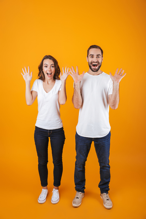 Full length photo of happy couple screaming in surprise while standing isolated over yellow background Stock Photo
