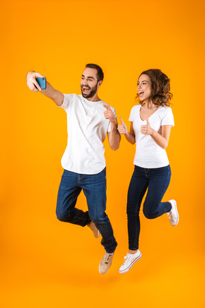 Foto a tutta lunghezza di una giovane coppia che ride e si fa selfie su smartphone isolato su sfondo giallo Archivio Fotografico