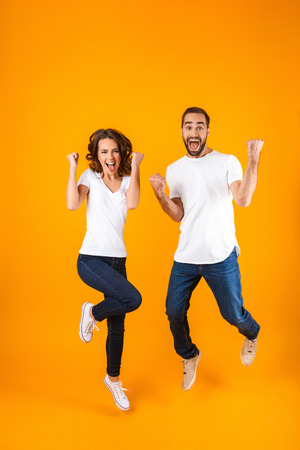 Full length photo of cheerful couple screaming in surprise while jumping isolated over yellow background
