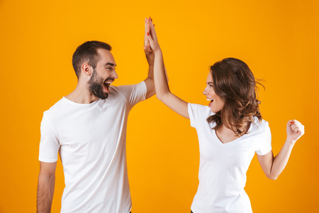 Image of young people man and woman in basic clothing slapping their hands together while standing isolated over yellow background