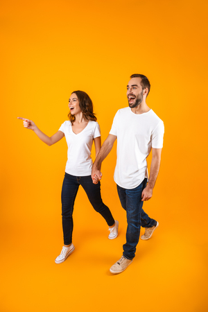 Full length photo of attractive couple smiling and walking isolated over yellow background Stock Photo