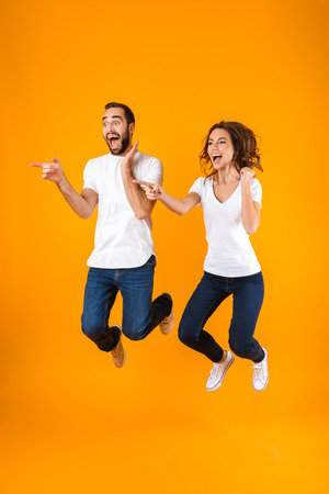 Full length photo of excited couple screaming in surprise while jumping isolated over yellow background Stock Photo