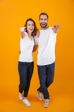 Full length photo of joyful couple smilings while standing isolated over yellow background