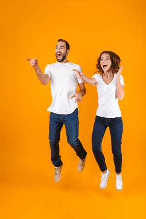 Full length photo of happy couple screaming in surprise while jumping isolated over yellow background Stock Photo