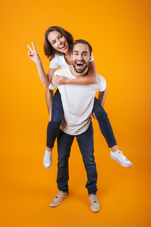 Full length image of beautiful couple having fun while man piggybacking joyful woman isolated over yellow background