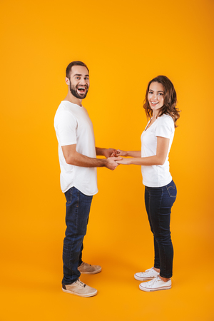 Full length photo of caucasian couple laughing and holding hands isolated over yellow background Stock Photo