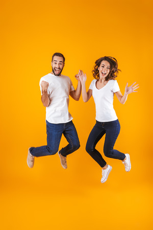 Full length photo of funny couple screaming in surprise while jumping isolated over yellow background