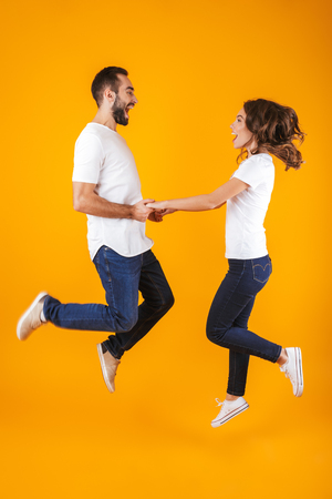 Full length photo of happy couple laughing and holding hands isolated over yellow background