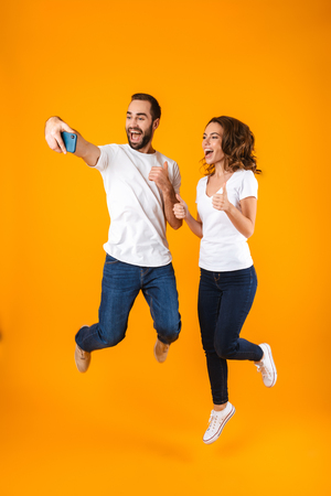 Full length photo of pleased couple laughing and taking selfie on smartphone isolated over yellow background