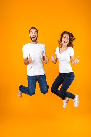 Full length photo of joyful couple screaming in surprise while jumping isolated over yellow background Stock Photo