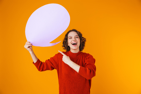 Image of attractive girl 20s wearing sweater holding thought bubble with copyspace while standing isolated over yellow background