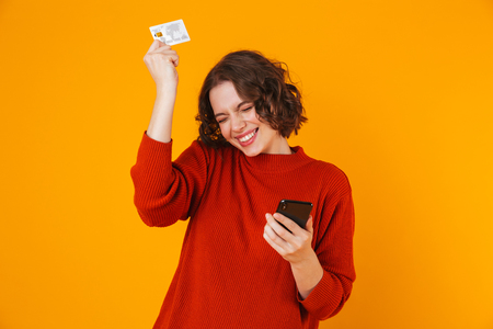 Bild der aufgeregten emotionalen jungen hübschen Frau, die lokalisiert über gelbem Wandhintergrund unter Verwendung des Handys posiert, das Kreditkarte hält.
