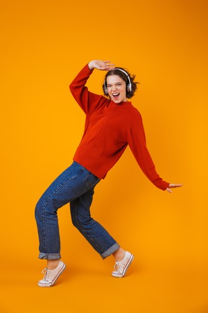Image of emotional young pretty woman posing isolated over yellow wall background listening music with headphones dancing.