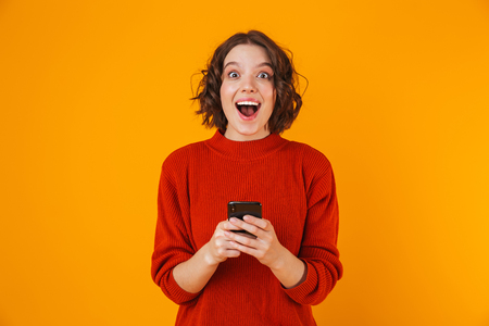 Portrait of caucasian woman 20s wearing sweater holding and using cell phone while standing isolated over yellow background